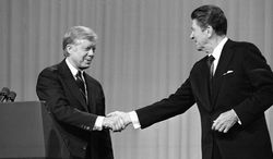 ** FILE ** In 1980: President Carter and Republican candidate Ronald Reagan shake hands after debating in Cleveland. (Associated Press)
