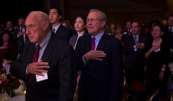 Former Secretary of Defense Donald Rumsfeld (right) holds his hand over his heart during the Pledge of Allegiance at the evening banquet as part of the 30th anniversary celebration of The Washington Times at the Marriott Wardman Park Hotel in Washington, D.C., Tuesday, Oct. 2, 2012. (Rod Lamkey Jr./The Washington Times)