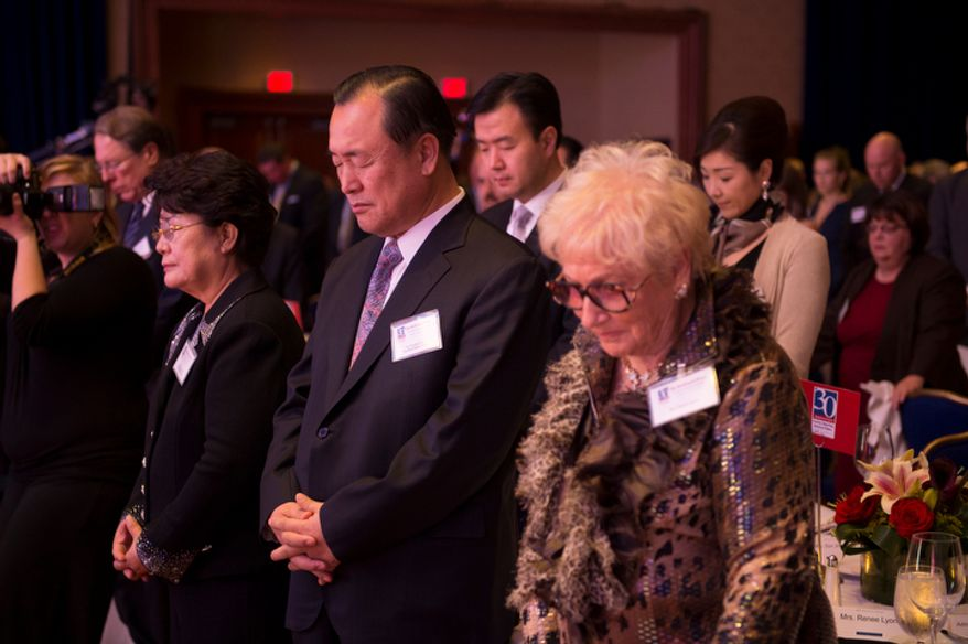 Dr. Douglas Joo (center) stands during a prayer at the evening banquet as part of the 30th anniversary celebration of The Washington Times at the Marriott Wardman Park Hotel in Washington, D.C., Tuesday, Oct. 2, 2012. (Rod Lamkey Jr./The Washington Times)