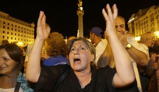 Opposition supporters react during a rally on the central square in Tbilisi Georgia, Monday, Oct. 1, 2012. (AP Photo / Efrem Lukatsky)