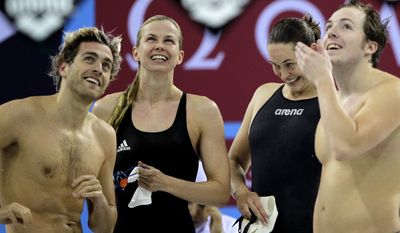 From left to right: Helge Folkert Meeuw, Britta Steffen, Jenny Mensing and Marco Koch from Germany celebrate after competing in the 4X50-meter medley relay short course race at the FINA/ARENA Swimming World Cup in Dubai, United Arab Emirates, Tuesday, Oct. 2, 2012. (AP Photo/Kamran Jebreili)