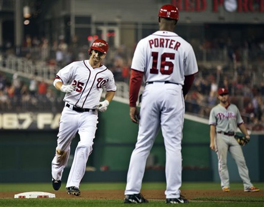 Washington Nationals' Adam LaRoche (25) rounds the bases after hitting a home run as third base coach Bo Porter (16) watches during the sixth inning of a baseball game against the Philadelphia Phillies in Washington, Tuesday, Oct. 2, 2012. The Nationals won 4-2. (AP Photo/Manuel Balce Ceneta)
