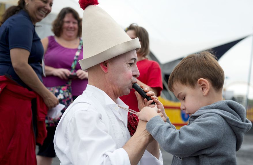 Matthew Dovi, 4, of McLean, feels the whistle while Pinot the clown (below) blows it outside the Big Apple Circus tent before a special Circus of the Senses performance in Sterling, Va. More than 1,200 saw the show, which was designed for children with sensory impairments. After the performances, they were given a chance to handle props. (Barbara L. Salisbury/The Washington Times)
