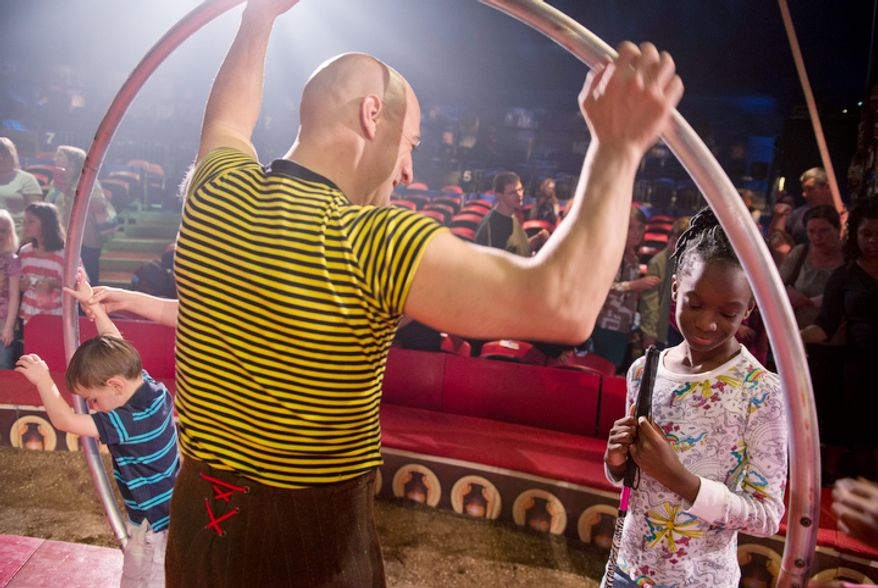 "Matthew Dovi, left, 4, of McLean, Va., and Kayla Harris, 9, of Lanham, Md., who are both blind, check out circus performer Daniel Cyr's giant hoop during a special ""touch session"" following the Big Apple Circus's ""Circus of the Senses"" performance on Wednesday, Oct. 3, 2012 in Sterling, Va. The show, which included sign language interpreters and headsets with play-by-play descriptions of the acts, was designed for visually and hearing impaired children.  (Barbara L. Salisbury/The Washington Times)"