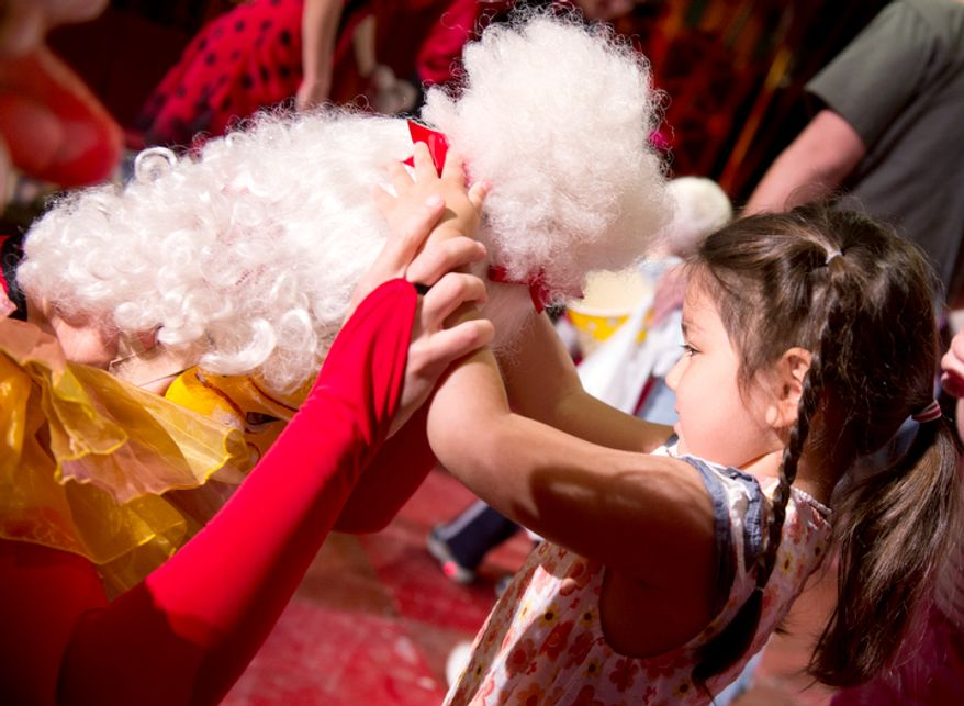"""Maria Zoerlein, 5, of Alexandria, Va., who is visually impaired, feels the wig of """"Madame"""" the clown (aka Christina Gelsone) during a special """"touch session"""" following the Big Apple Circus """"Circus of the Senses"""" performance on Wednesday, Oct. 3, 2012 in Sterling, Va. (Barbara L. Salisbury/The Washington Times)"""