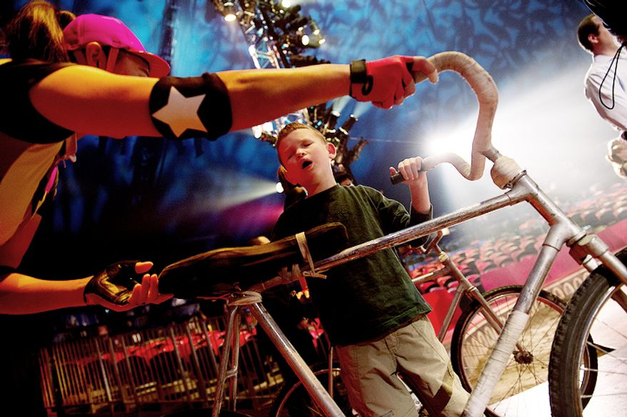 "Max Smith-Levin, 7, of Warrenton, Va., feels one of the bicycles from the Dalian Acrobatic Troupe during a special ""touch session"" following the Big Apple Circus's ""Circus of the Senses"" performance on Wednesday, Oct. 3, 2012 in Sterling, Va. Max is one of the visually impaired audience members who was invited into the ring after the show to get an up-close look at some of the props and costumes. (Barbara L. Salisbury/The Washington Times)"