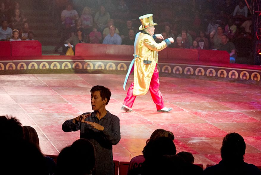 "Susan Thompson-Gaines, left, uses American Sign Language to interpret the action in the ring for the hearing impaired audience members at the Big Apple Circus's special ""Circus of the Senses"" performance on Wednesday, Oct. 3, 2012 in Sterling, Va. This is the 13th time that the circus has held such a show; the first was in 2000. According to circus founder Paul Binder, it's just part of the circus's way of giving back. (Barbara L. Salisbury/The Washington Times)"