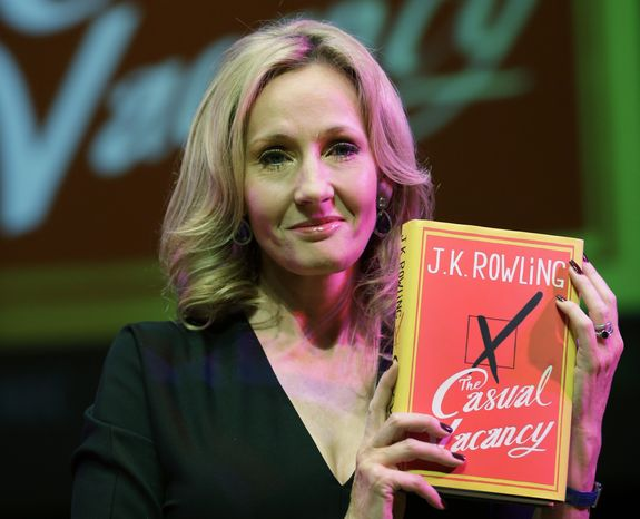 """""""Harry Potter"""" author J.K. Rowling poses with her new book, the adult novel """"The Casual Vacancy,"""" at the Southbank Centre in London on Thursday, Sept. 27, 2012. (AP Photo/Lefteris Pitarakis)"""