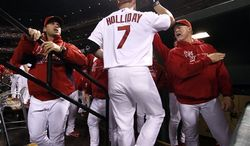St. Louis Cardinals' Matt Holliday is congratulated by manager Mike Matheny, left, and hitting coach Mark McGwire, right, after driving in a run with a sacrifice fly during the first inning of a baseball game against the Cincinnati Reds on Tuesday, Oct. 2, 2012, in St. Louis. (AP Photo/St. Louis Post-Dispatch, Chris Lee)