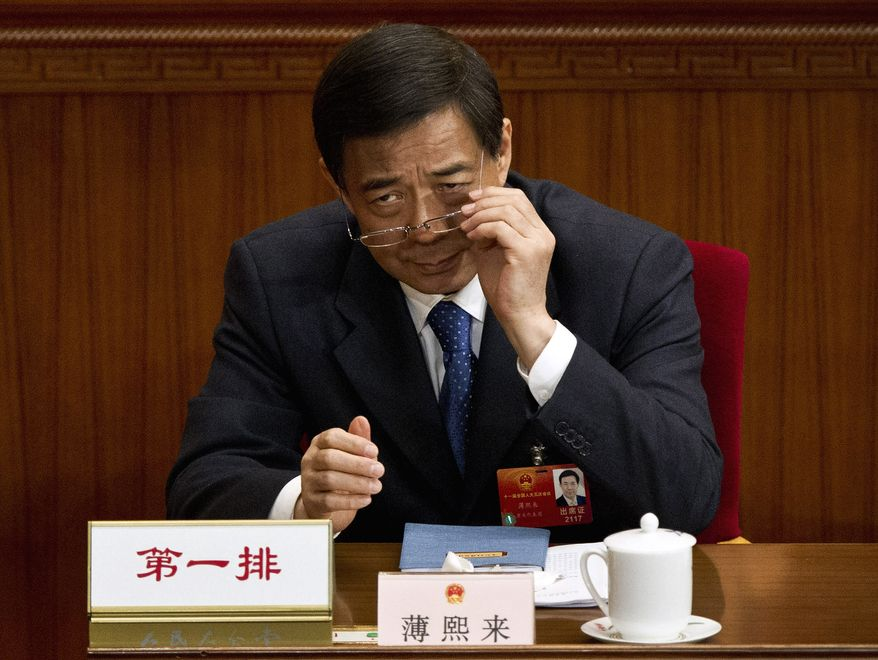** FILE ** Then-Chongqing Party Secretary Bo Xilai puts on his glasses during a plenary session of the National People's Congress at the Great Hall of the People in Beijing on Monday, March 11, 2012. (AP Photo/Andy Wong)