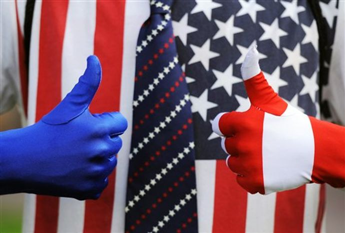 Chris Bandrowsky, 20, of Denver, dressed in red, white and blue, gives the thumbs up while having his picture taken at DebateFest at the University of Denver on Wednesday, Oct. 3, 2012, in Denver, before the first presidential debate between President Barack Obama and Republican challenger Mitt Romney. (AP Photo/Chris Schneider)