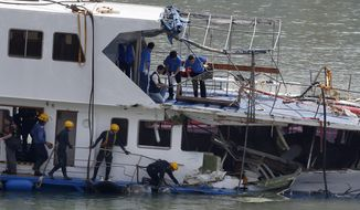 Firemen and police officers investigate on a salvaged boat that sank after colliding with a ferry near Lamma Island, off the southwestern coast of Hong Kong Island, on Wednesday, Oct. 3, 2012. (AP Photo/Kin Cheung)