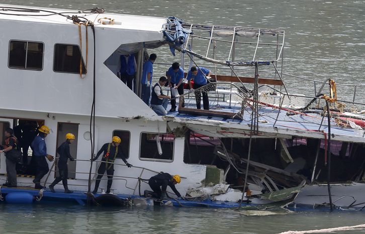 Firemen and police officers investigate on a salvaged boat that sank after colliding with a ferry near Lamma Island, off the southw