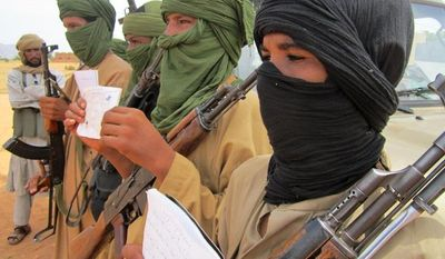 Young fighters, including 13-year-old Abdullahi (right) and 14-year-old Hamadi (second right), display their Quranic studies notes for a journalist as their Islamist commanders watch in Douentza, Mali, on Sept. 27, 2012. (Associated Press)