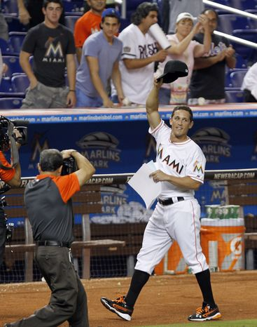 Miami Marlins' Adam Greenberg acknowledges the fans after the Marlins won 4-3 against the New York Mets in 11 innings of a baseball game in Miami, Tuesday, Oct. 2, 2012. Greenberg struck out on three pitches against Mets R.A. Dickey when he batted for the first time in seven years in the sixth inning. Greenberg signed a one-day contract before the game, his first since he was beaned in his major league debut in 2005. (AP Photo/Alan Diaz)
