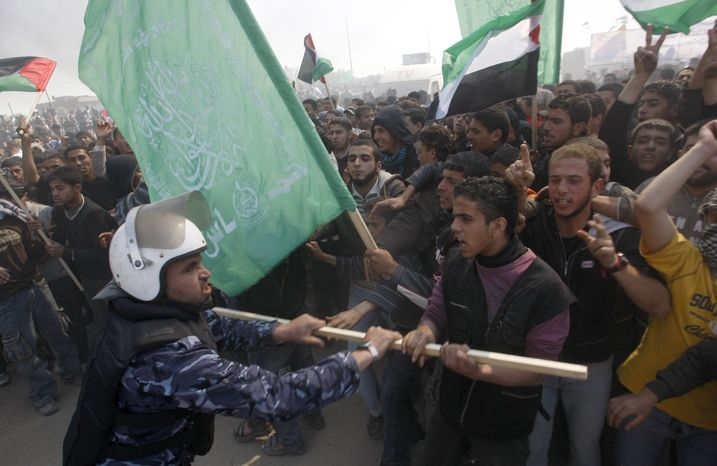 FILE - In this March 30, 2012 file photo, a Hamas security officer tries to prevent protesters from reaching Erez crossing during a march heading towards the border with Israel in the northern Gaza Strip. (AP Photo/Hatem Moussa, File)