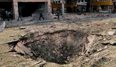 In this photo released by the Syrian official news agency SANA, Syrians walk past a crater caused by an explosion at the scene where triple bombs exploded at the Saadallah al-Jabri square, in Aleppo, Syria, on Oct. 3, 2012. (Associated Press/SANA)