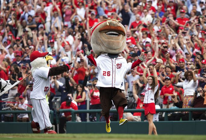 Teddy Roosevelt, one of the Washington Nationals' racing presidents, celebrates after crossing the finish line winning the Presidents Race for the first time in the event's seven-year history at Nationals Park during a baseball game between the Washington