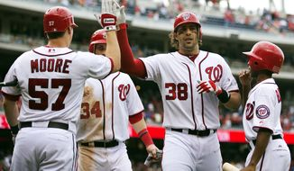 Washington Nationals' Michael Morse (38) is congratulated by Tyler Moore (57) after hitting a home run during the eighth inning of a baseball game against the Philadelphia Phillies in Washington, Wednesday, Oct. 3, 2012. The National won 5-1. (AP Photo/Manuel Balce Ceneta)