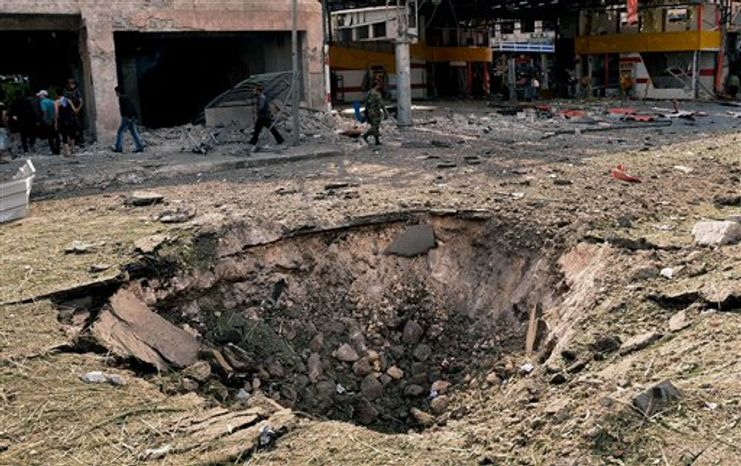 In this photo released by the Syrian official news agency SANA, Syrians walk past a crater caused by an explosion at the scene where triple bombs exploded at the Saadallah al-Jabri square, in Aleppo city, Syria, Wednesday, Oct. 3, 2012. (AP Photo/SANA)