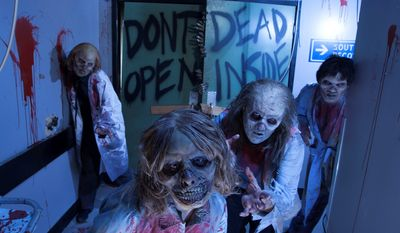 """This image provided by Universal Orlando Resort shows actors portraying zombies at an attraction themed on the AMC show """"The Walking Dead"""" at Universal's Halloween Horror Nights in Orlando, Fla. (AP Photo/Universal Orlando Resort, Kevin Kolczynski)"""