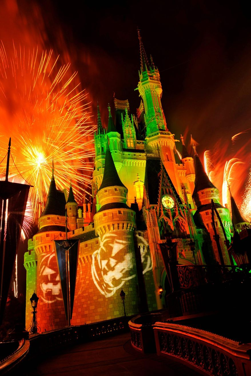 """Fireworks explode over Cinderella's Castle while illuminated pumpkins are projected with light during the """"Happy HalloWishes"""" fireworks show at Walt Disney World's Magic Kingdom in Lake Buena Vista, Fla. (AP Photo/Disney, Gene Duncan)"""
