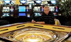 A man plays slot machine roulette in a gambling hall in Budapest, Hungary, Wednesday, Oct. 3, 2012. Hungary's ban on slot machines has taken the country's gambling industry by surprise. (AP Photo/Bela Szandelszky)