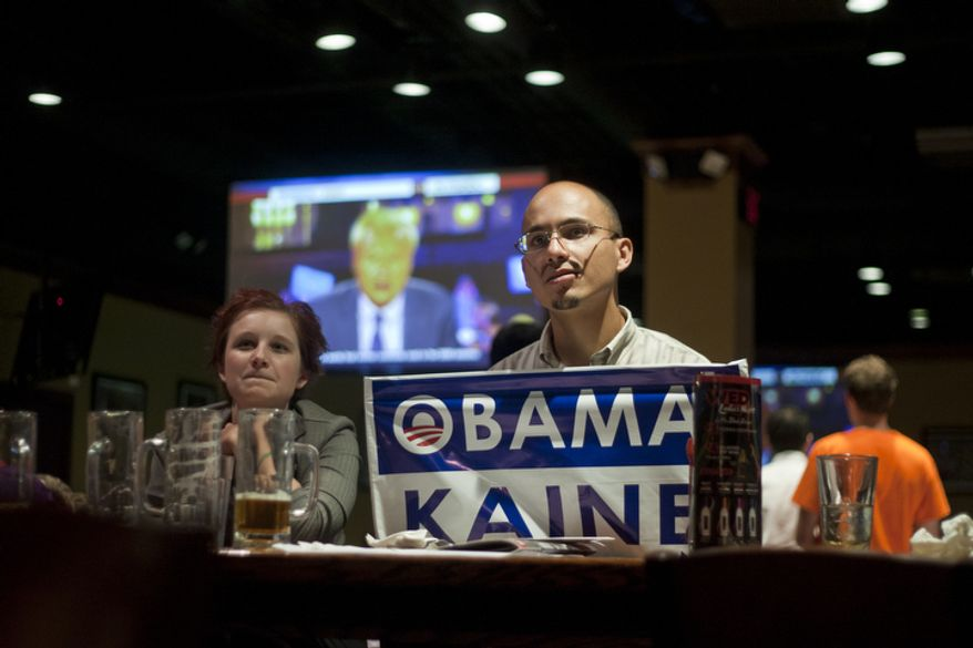 Alyssa Boffey, left, and Tony Robinson, right, watch the first presidential debate between President Obama and Republican nominee Mitt Romney during a watch party put on by the Arlington Young Democrats and the Arlington County Democratic Committee at Bailey's Pub in Ballston Common Mall, Ballston, Va., Wednesday, Oct. 3, 2012. (Craig Bisacre/The Washington Times)