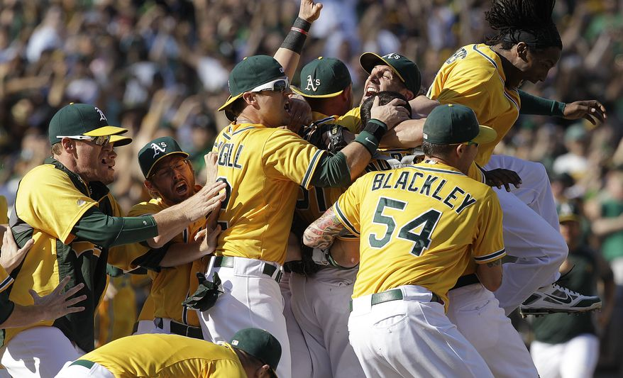 Oakland Athletics players celebrate after clinching the American League West at the end of their 12-5 win over the Texas Rangers in a baseball game, Wednesday, Oct. 3, 2012, in Oakland, Calif. (AP Photo/Ben Margot)