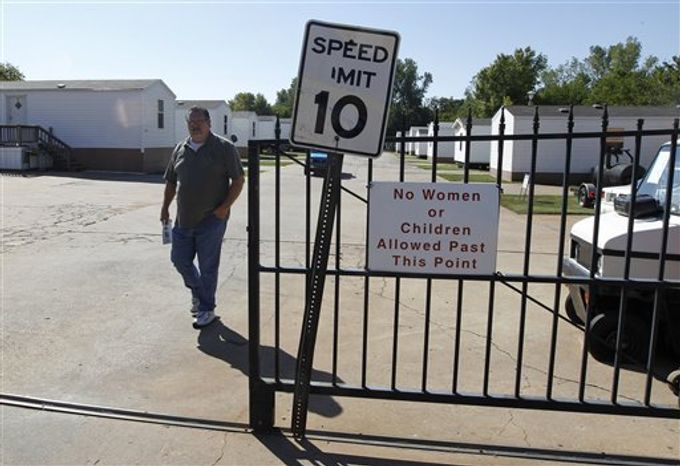 James Womack, director of Hand Up Ministries, walks through the gate which has a sign prohibiting women or children inside the community, in Oklahoma City, Wednesday, Oct. 3, 2012. Hand Up Ministries is a non profit faith-based organization that offers help to men and women coming out of the prison system to re-enter society. The grounds currently house 150 sex offenders and 7 other felons. (AP Photo/Sue Ogrocki)