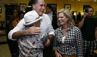 Republican presidential candidate and former Massachusetts Gov. Mitt Romney gets a hug from a patron as he campaigns with his wife Ann during an unscheduled stop at La Teresita, a Cuban restaurant, in Tampa, Fla., Friday, Oct. 5, 2012. (AP Photo/Charles Dharapak)