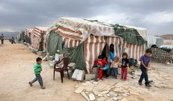 **FILE** Syrian refugees children stand Oct. 2, 2012, in front of their tents at a refugee camp in Arsal, a Sunni Muslim town eastern Lebanon near the Syrian border that has become a safe haven for war-weary Syrian rebels and hundreds of refugee families. (Associated Press)