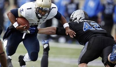 Navy quarterback Trey Miller, left, runs for yardage as Air Force linebacker Austin Niklas comes in for a tackle during the first quarter of an NCAA college football game at Air Force Academy, Colo., on Saturday, Oct. 6, 2012. (AP Photo/David Zalubowski)