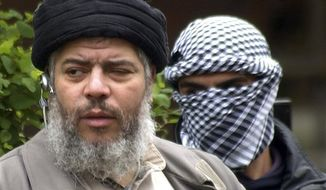 ** FILE ** This Friday, April 30, 2004, file photo shows Muslim cleric Abu Hamza al-Masri, as he arrives with a masked bodyguard, right, to conduct Friday prayers in the street outside the closed Finsbury Park Mosque in London. (AP Photo/Max Nash, File)