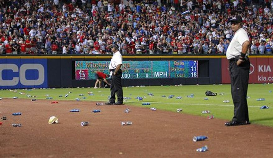 Atlanta Braves officials pick up trash on the field as security stand by during the eighth inning of the National League wild card playoff baseball game against the St. Louis Cardinals, Friday, Oct. 5, 2012, in Atlanta. The Cardinals won baseball's first wild-card playoff, taking advantage of a disputed infield fly call that led to a protest and fans littering the field with debris, to defeat the Braves 6-3. (AP Photo/Todd Kirkland)