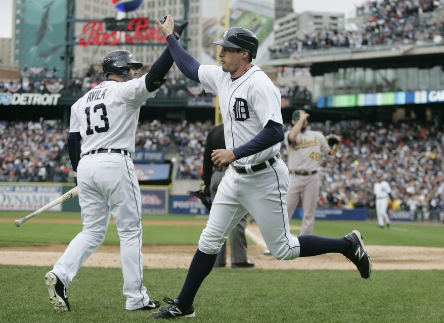 Detroit Tigers' pinch runner Don Kelly, right, is met at the dugout by teammate Alex Avila after scoring on a wild pitch by Oakland Athletics relief pitcher Ryan Cook during the eighth inning of Game 2 of the American League division baseball series, Sunday, Oct. 7, 2012, in Detroit. (AP Photo/Duane Burleson)