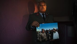 On Tuesday, Oct. 2, 2012, in Kabul, Afghanistan, Afghan Gen. Majid Rouzi, a former civil war commander who now is an adviser to the Ministry of Interior, shows off his favorite civil war photograph, in which he is pictured with one of the best-known Afghan military leaders, Ahmad Shah Massoud. (AP Photo/Dusan Vranic)