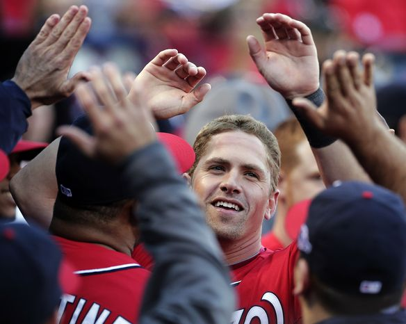 Washington Nationals' Tyler Moore celebrates in the dugout after hitting a two-RBI single during the eighth inning of Game 1 of the National League division baseball series against the St. Louis Cardinals, Sunday, Oct. 7, 2012, in St. Louis. (AP Photo/Charlie Riedel)