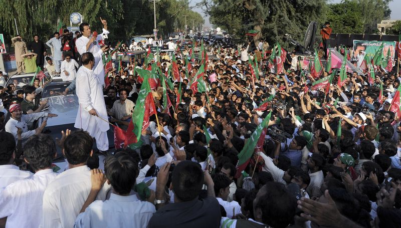 Imran Khan (top left), a Pakistani cricket-star-turned-politician, addresses supporters during a peace march in Mianwali, Pakistan, on Saturday, Oct. 6, 2012. Thousands of Pakistanis joined by a group of U.S. anti-war activists headed toward Pakistan's militant-riddled tribal belt Saturday to protest U.S. drone strikes, even as a Pakistani Taliban faction warned that suicide bombers would stop the demonstration. (AP Photo/Jabbar Ahmed)