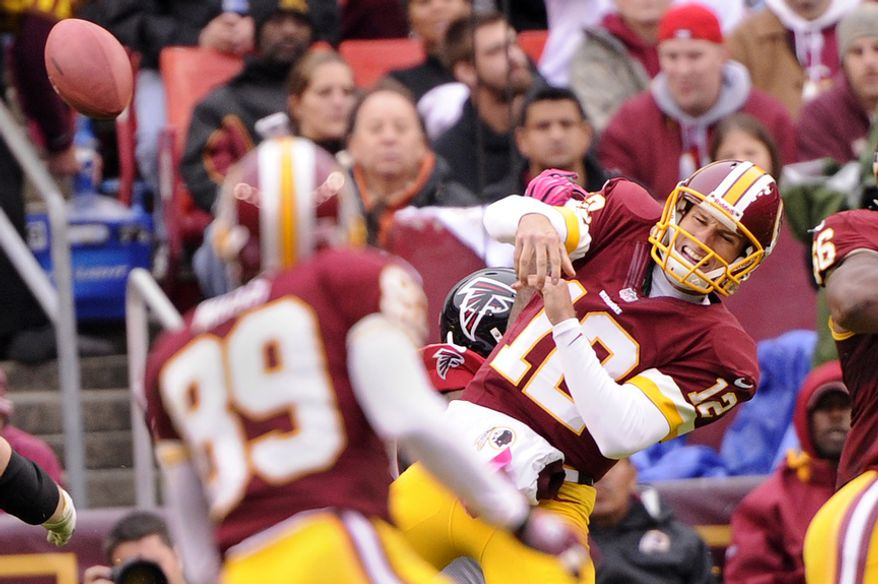 Washington Redskins quarterback Kirk Cousins (12) is hit as he tries to pass in the third quarter at FedEx Field in Landover, Md., on Sunday, Oct. 7, 2012. (Preston Keres/Special to The Washington Times)