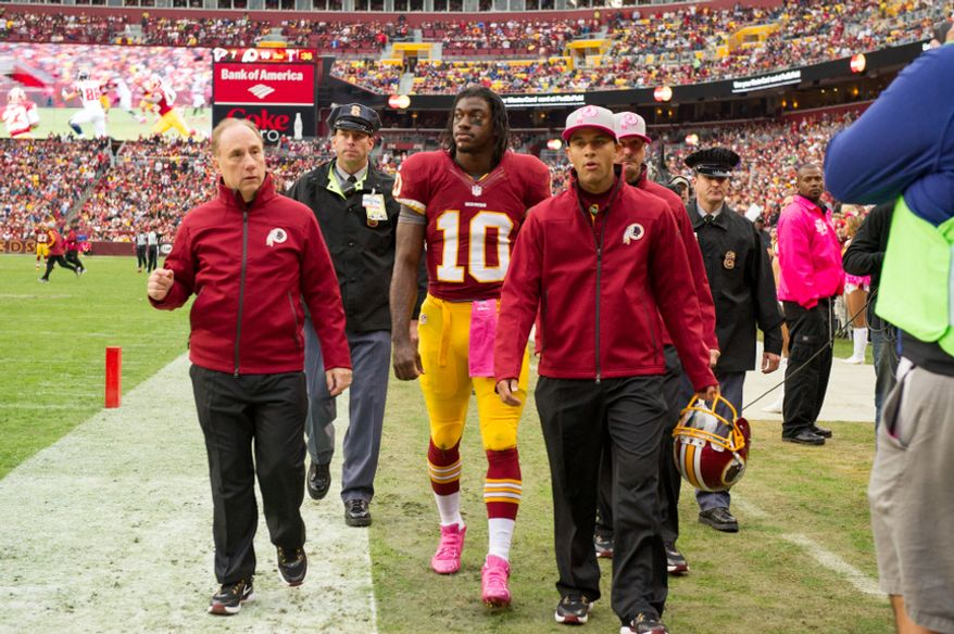 Washington Redskins quarterback Robert Griffin III is taken to the locker room after being hit hard in the third quarter during the Redskins' 24-17 loss to the Atlanta Falcons on Oct. 7, 2012, at FedEx Field in Landover, Md. (Andrew Harnik/The Washington Times)
