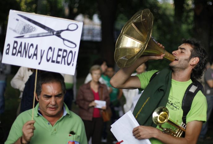 "A protester holds a banner that translates as ""Financial cuts to banks and church"" in Madrid on Saturday, Oct. 6, 2012, as another shouts slogans against health care austerity measures announced by the Spanish government. (AP Photo/Andres Kudacki)"