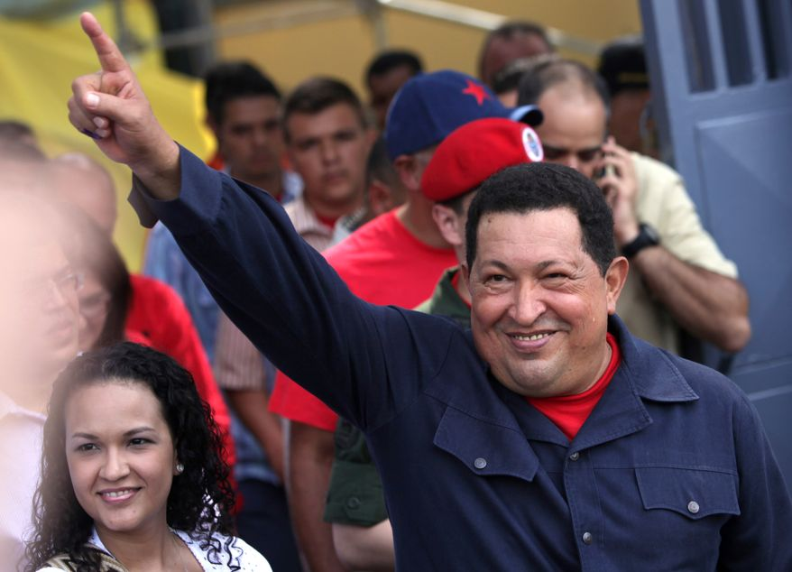 Venezuelan President Hugo Chavez, accompanied by his daughter, Rosa Virginia (left), gestures to supporters Oct. 7, 2012, as he leaves the polling station after voting in the presidential election in Caracas, Venezuela. Chavez is running for re-election against opposition candidate Henrique Capriles. (Associated Press)