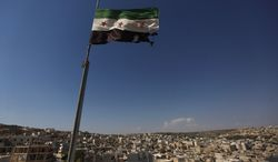 FILE - In this Tuesday, June 12, 2012 file photo, a Syrian revolutionary flag waves on top of a building on the outskirts of Aleppo, Syria. Syria's conflict is the most violent to emerge from last year's Arab Spring. The protests started peacefully but prompted a brutal crackdown by President Bashar Assad's government. The fighting has escalated into a civil war that has killed just over 30,000 people over the last year and a half, according to activists. Despite intervening in Libya, the United States has steered clear of taking military action or arming Syria's rebels. (AP Photo/Khalil Hamra, File)