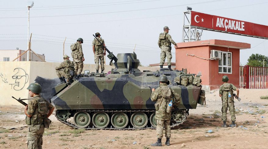 Turkish soldiers at a military station in Akcakale, Turkey, guard the border gate with Syria across from the rebel-controlled town of Tel Abyad on Sunday. Turkey sent more artillery to hot spots along the troubled border on Monday. (Associated Press)