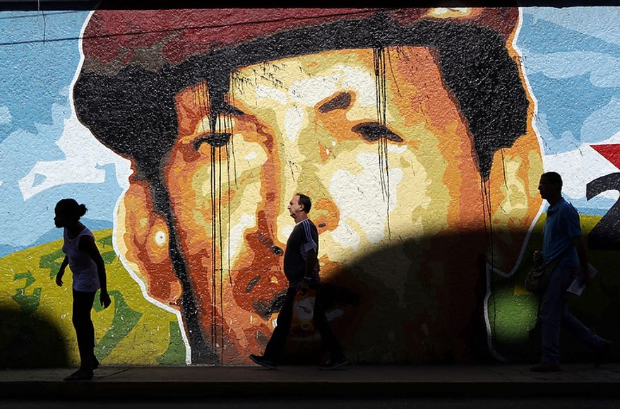 People walk past a mural depicting Venezuelan President Hugo Chavez in Caracas, Venezuela, on Monday, Oct. 8, 2012. Mr. Chavez won re-election and a new endorsement of his socialist project Sunday, surviving his closest race yet after a bitter campaign against opposition candidate Henrique Capriles. (AP Photo/Rodrigo Abd)