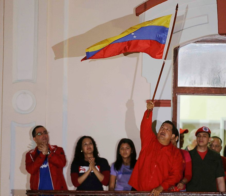 Venezuelan President Hugo Chavez waves a Venezuelan flag as he greets supporters at the Miraflores Palace balcony in Caracas, Venezuela, on Sunday, Oct. 7, 2012. Mr. Chavez won re-election and a new endorsement of his socialist project, surviving his closest race yet after a bitter campaign against opposition candidate Henrique Capriles. (AP Photo/Fernando Llano)