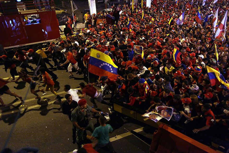 Supporters of President Hugo Chavez run toward the Miraflores Palace as they celebrate in Caracas, Venezuela, on Sunday, Oct. 7, 2012. Venezuela's electoral council said late Sunday that President Hugo Chavez had won re-election, defeating challenger Henrique Capriles. (AP Photo/Rodrigo Abd)