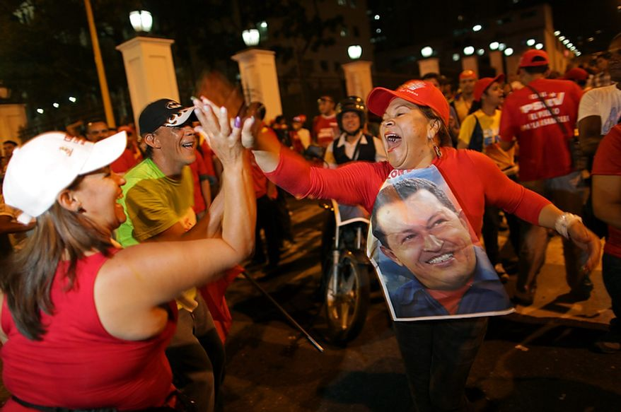 Supporters of Venezuelan President Hugo Chavez cheer after polling stations closed and before any results were made available in Caracas, Venezuela, on Sunday, Oct. 7, 2012. The country's electoral council later said Mr. Chavez had won re-election, defeating challenger Henrique Capriles. (AP Photo/Rodrigo Abd)