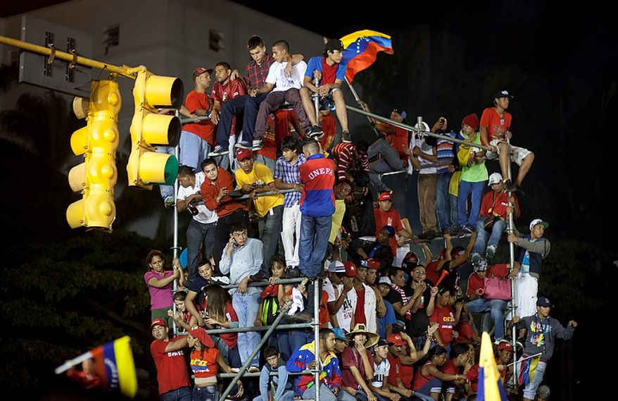 Supporters of President Hugo Chavez celebrate outside the Miraflores Palace in Caracas, Venezuela, on Sunday, Oct. 7, 2012. Venezuela's electoral council said late Sunday that Mr. Chavez had won re-election, defeating challenger Henrique Capriles. (AP Photo/Ramon Espinosa)